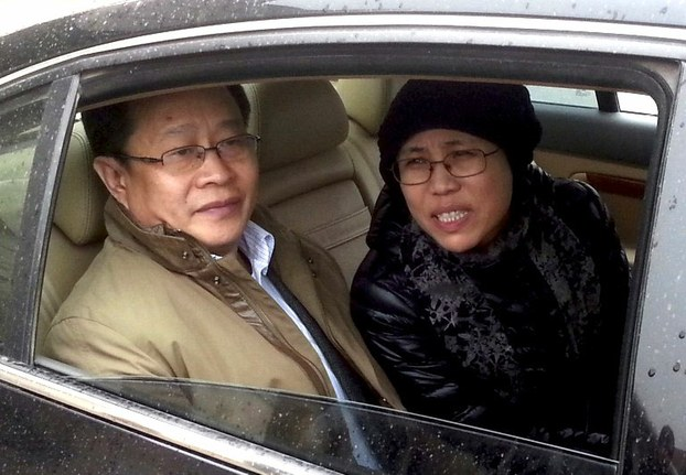 Liu Xia (r) and rights lawyer Mo Shaoping (l) arrive at her brother Liu Hui's trial in Beijing on April 23, 2013.