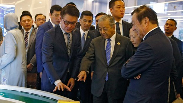 Prime Minister Mahathir Mohamad (second from right) and Huawei founder and CEO Ren Zhengfei (right) look at a parcel-handling machine during the Malaysian leader's visit to Beijing, April 25, 2019.