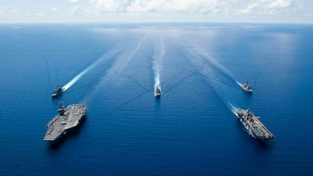 The aircraft carrier USS Ronald Reagan (left) and other ships from the U.S. Navy's 7th Fleet sail in formation in the South China Sea, Oct. 6, 2019.