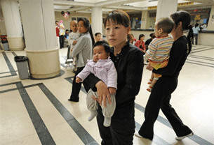 BEIJING, China: Mothers hold their babies at a children's hospital in Beijing as China's toxic milk scandal escalates, 23 September 2008.
