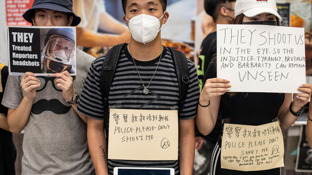 Protesters hold placards at Hong Kong's International Airport, Aug. 12, 2019.