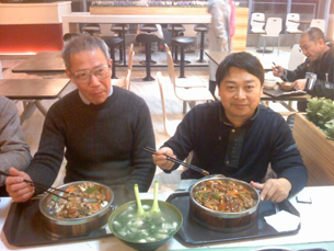 Qin Yongmin (L) is treated to a welcome home dinner by his friend Chen Yunfei (R).