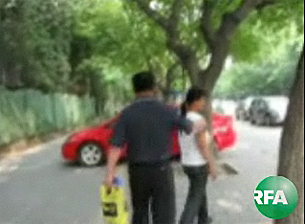 A protester in Beijing's Ritan Park is detained by police and escorted away from an interview with RFA.