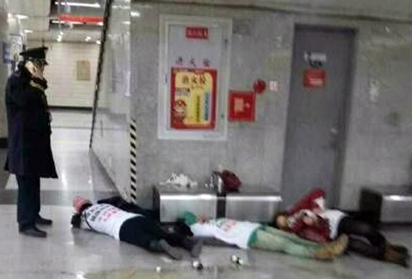 Three women lie slumped on a subway platform at Beijing's Tiananmen East station after ingesting pesticides in protest over a phone scam, Nov. 24, 2016.