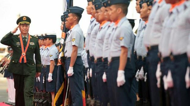 China's Coast Guard chief, Maj. Gen. Wang Zhongcai, reviews an honor guard during his arrival at the Philippine Coast Guard headquarters in Manila, Jan. 14, 2020.