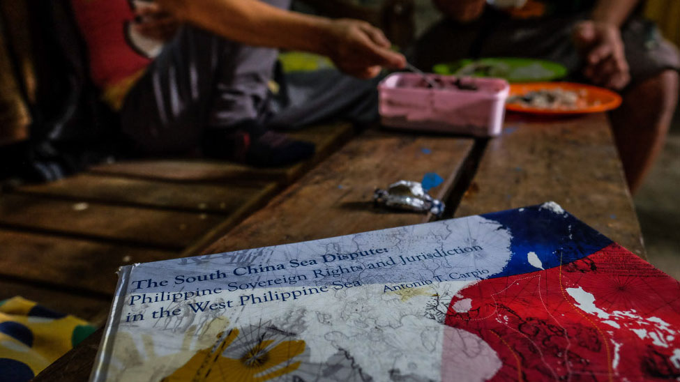 A book about an international court case in a territorial dispute over Scarborough Shoal sits on a bench in Johnny Sonny Geruela's home as he and his wife share a meal, Sept. 6, 2019.