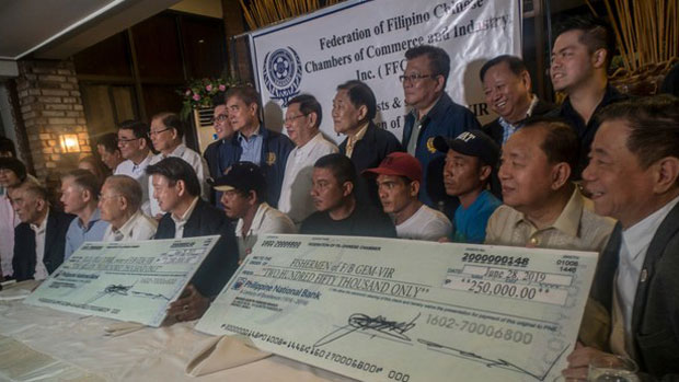 Members of the Federation of Filipino Chinese Chambers of Commerce and Industry present checks in Manila to Filipino fishermen whose boat was rammed by a Chinese trawler earlier this month, June 28, 2019.