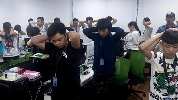 n this handout photo provided by the Philippine Bureau of Immigration, foreign nationals, mostly Chinese, put their hands on their heads during a raid of their company premises in Manila, Oct. 10, 2019.