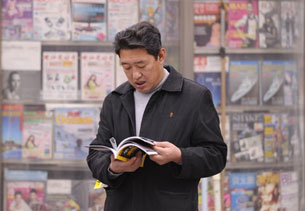 A man reads a magazine beside a newsstand in Beijing in a file photo.