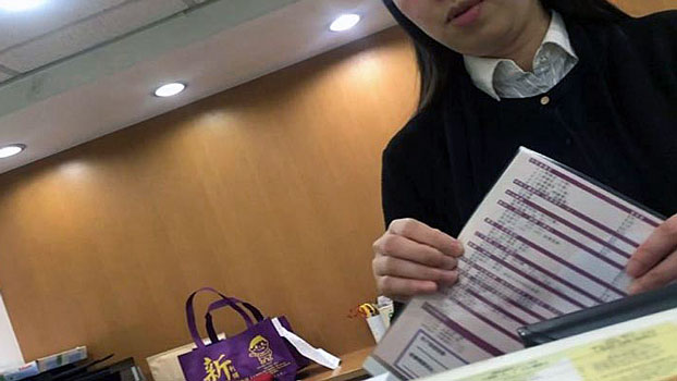 An employee at a firm providing business registration services in Hong Kong's central business district produces a document with procedures for mainland Chinese to open shell companies, saying that her firm would not ask any questions, December 2018.