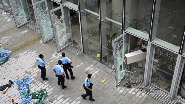 Police stand outside the Legislative Council building in Hong Kong inspecting damage after protesters broke into the building, July 2, 2019.