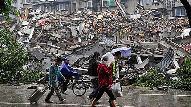 Residents of Dujiangyan in China's Sichuan province walk past an earthquake-collapsed building, May 13, 2008.