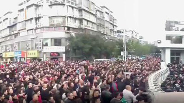Screenshot of a large crowd pushing against the gates of the county government building in Sichuan's Rongxian county, with uniformed officers pushing back, after an earthquake triggered anger about fracking, Feb. 25, 2019.
