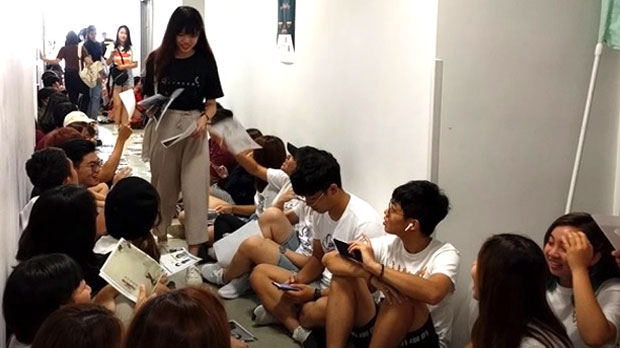 Hong Kong Baptist University students distribute leaflets condemning the arrest of student union leader Keith Fong, Aug. 8, 2019.