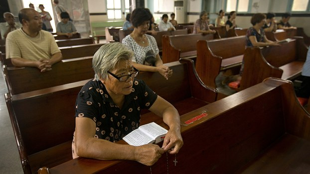Parishioners hold an impromptu prayer vigil as they wait for Chinese authorities to cut down their church's cross in Zhejiang province's Yongjia county, in a file photo.