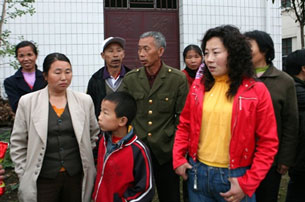 Family members gather outside a kindergarten where seven children and a teacher were hacked to death with a cleaver in Nanzheng, May 12, 2010.