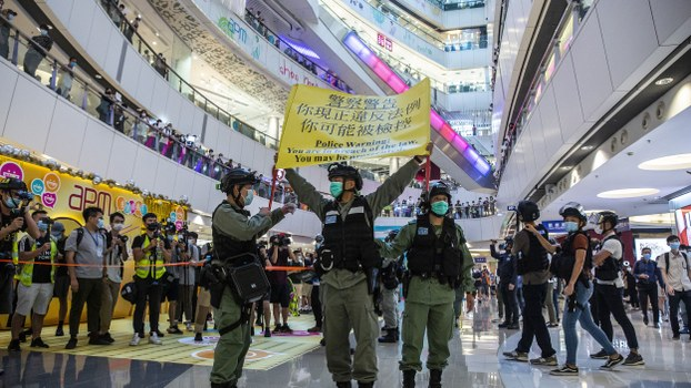 Police in Hong Kong hold up a flag warning protesters in a shopping mall to disperse, July 6, 2020.