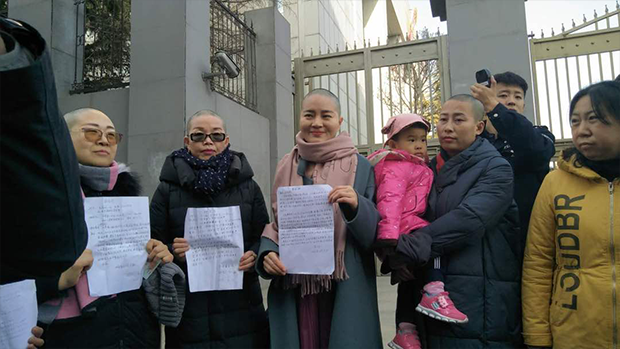 The wives of four Chinese activists hold a 'shaved-head protest' outside of China's Supreme Court in Beijing, Dec. 17, 2018.