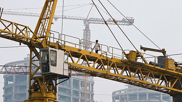 Worker walks on a crane at a Beijing construction site in a file photo.