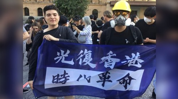 University of Queensland student Drew Pavlou (L) holds a banner supporting Hong Kong's pro-democracy movement in an undated photo.