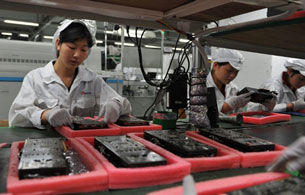 Workers inspect motherboards on a factory line at the Foxconn plant in Shenzen, May 26, 2010.