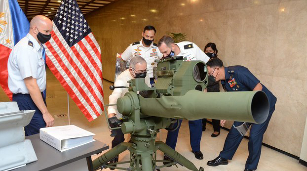 Philippines foreign secretary Teodoro Locsin Jr. (seated) examines a target-acquisition system delivered by US National Security Adviser Robert O'Brien in Manila, Nov. 23, 2020.