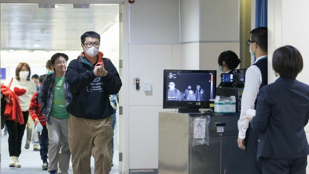 """Taiwan's Center for Disease Control (CDC) personnel use thermal scanners to screen passengers arriving on a flight from China's Wuhan province, where a SARS-like virus was discovered and has since spread, at the Taoyuan International Airport,"""" Jan. 13, 2020."""
