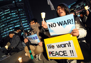 Activists hold anti-war placards during a candlelight rally in Seoul, Dec. 20, 2010.