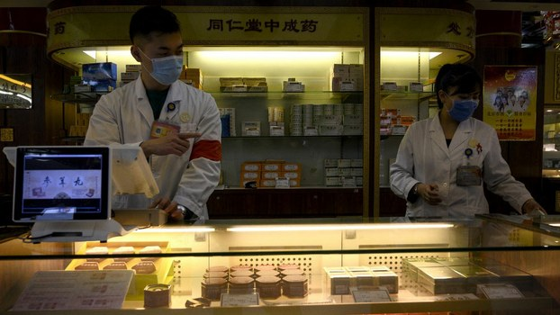 Employees wear protective face masks at a traditional Chinese medicine store in Beijing, Feb. 1, 2020.