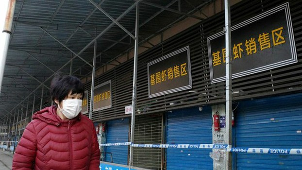 A woman walks past the closed meat and seafood market in Wuhan, China, that has been linked to a new coronavirus outbreak that has spread to Thailand, Jan. 12, 2020.