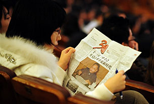 A woman reads a newspaper featuring the 30th anniversary of China's economic reform era in Beijing, December 2008.