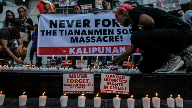 Philippine activists light candles outside the Chinese Embassy in Manila's financial district to mark the 30th anniversary of the Tiananmen Square massacre, June 4, 2019.