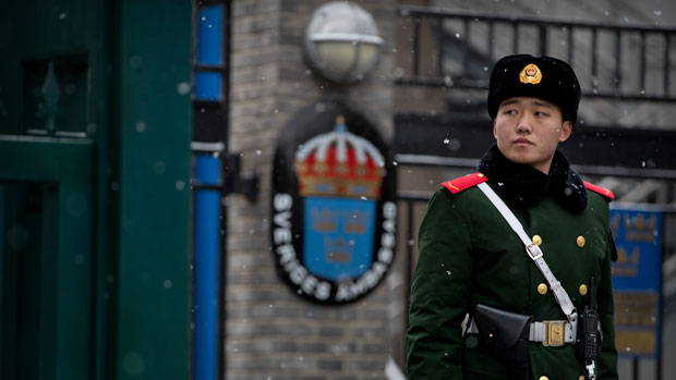 A Chinese police officer stands guard at the entrance to the Swedish embassy in Beijing, Feb. 14, 2019.