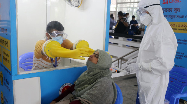 Medical workers collect samples for a COVID-19 test at a temporary isolation center in Dhaka, Bangladesh, July 20, 2020.