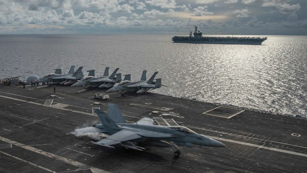 A U.S. F/A-18E Super Hornet fighter jet lands on the flight deck of the USS Ronald Reagan as the USS Nimitz steams alongside during drills by the two aircraft carriers in the South China Sea, July 6, 2020.