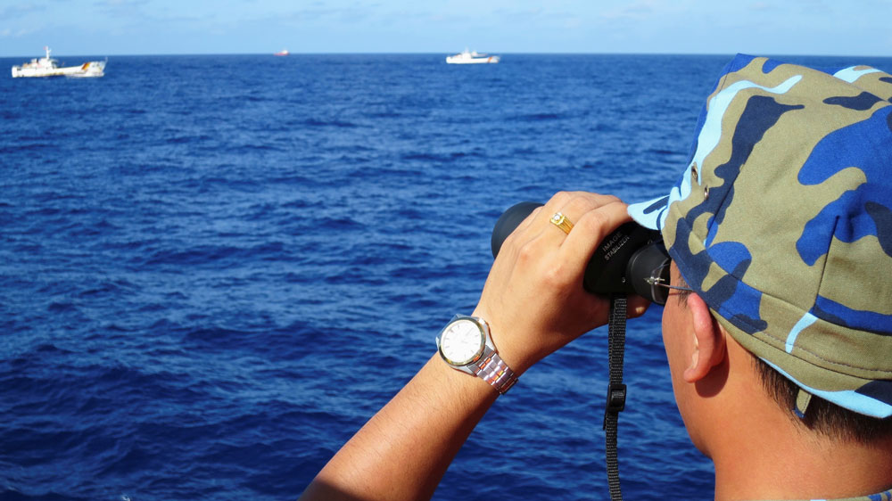 A crewman from the Vietnamese coastguard ship looks out at sea as Chinese coastguard vessels give chase to Vietnamese ships near an oil rig in the South China Sea in a file photo from July 2014.