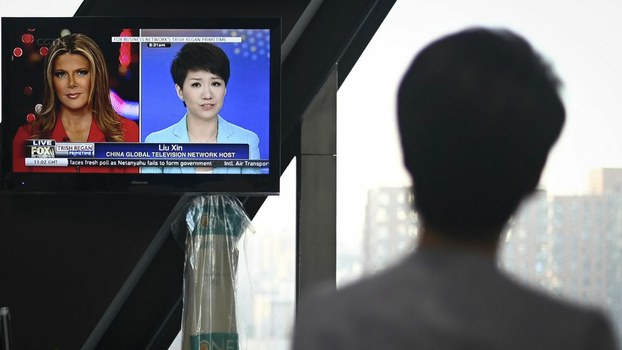 China's state broadcaster CGTN anchor Liu Xin looks at a screen showing her debate with Fox Business Network presenter Trish Regan, at the CCTV headquarters in Beijing, May 30, 2019.