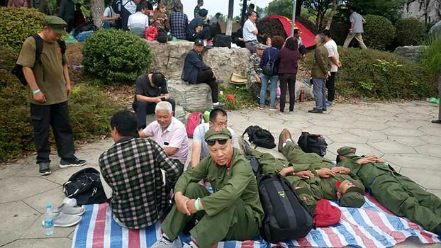 Veterans sit on the ground during a rally in Zhenjiang in eastern China's Jiangsu province, June 22, 2018.