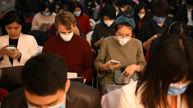 Journalists wear protective face masks during a National Health Commission press conference in Beijing, Jan. 27, 2020.