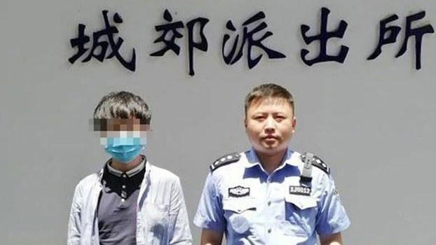 A man surnamed Yang (L) stands with a policeman at The Hanbin district police department in Shaanxi's Ankang city, which fined Yang 500 yuan for using a VPN to  scaling China's complex systems of blocks, filters and human censorship that limits what Chinese users can see online, May 19, 2020.