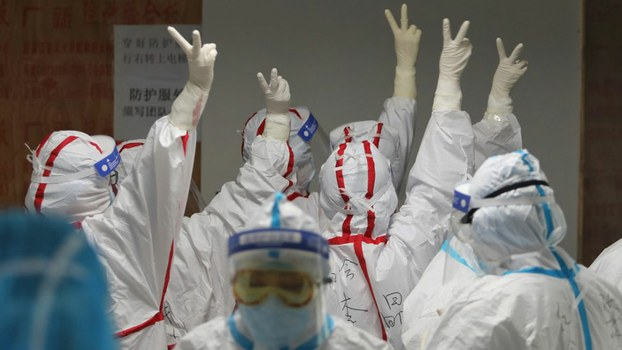 Medical staff cheer themselves up before going into an ICU ward for COVID-19 coronavirus patients at the Red Cross Hospital in Wuhan in China's central Hubei province, March 16, 2020.