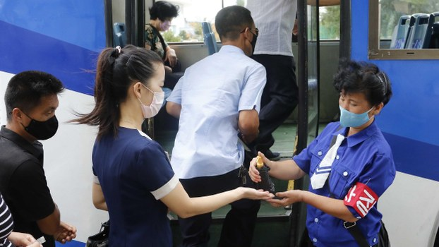 A passenger has her hands disinfected before getting on a trolley bus in Pyongyang, North Korea, Thursday, Aug. 13, 2020.