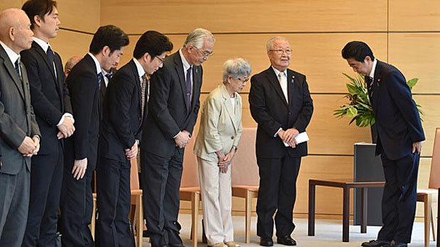 Japanese prime minister Shinzo Abe (R) bows to the leader of a group of families of Japanese citizens abducted by North Korea, June 14, 2018.