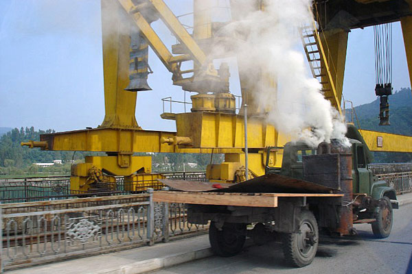 A charcoal-powered truck belches smoke as it passes over a bridge near Hyangsan in North Pyongan province, North Korea, in a file photo.