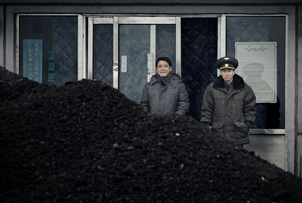 A North Korean officer (R) and another man stand behind a pile of coal along the banks of the Yalu River in the northeastern city of Siniuju, Dec. 14, 2012.