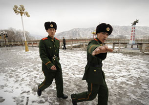 A Chinese border guard tries to stop his picture from being taken along the Tumen River, March 21, 2009.