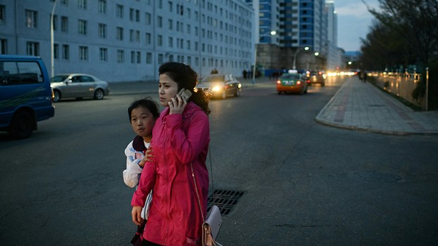 A woman speaks on a mobile phone as she walks with a child in Pyongyang, April 15, 2018.