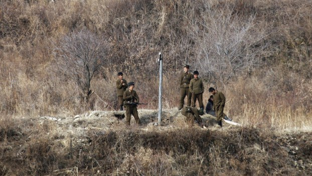 North Korean border guards stand in a field at the Yalu River near the North Korean city of Hyesan, which borders China's Changbai county, in a file photo.