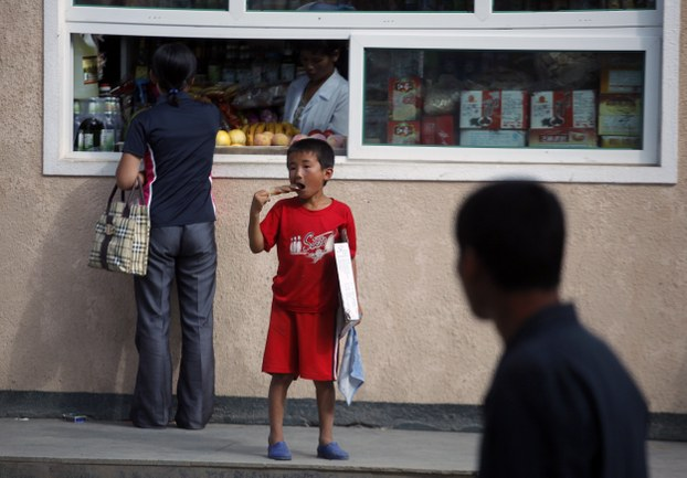 A boy eats ice cream near a local market at North Korean Special Economic Zone of Rason city, located northeast of Pyongyang in a file photo.