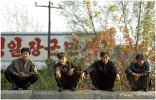 A North Korean soldier (2L) squats with civilians on the bank of the Yalu River in the North Korean town of Sinuiji, 18 October 2006, in this picture taken from the opposite side on the Chinese border city of Dandong.
